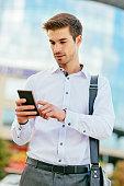 Businessman using smartphone on the street