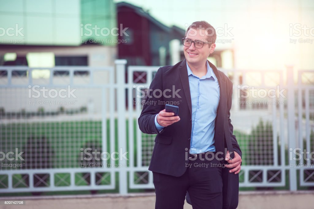 Businessman using Smartphone Walking outside of Office Building stock photo
