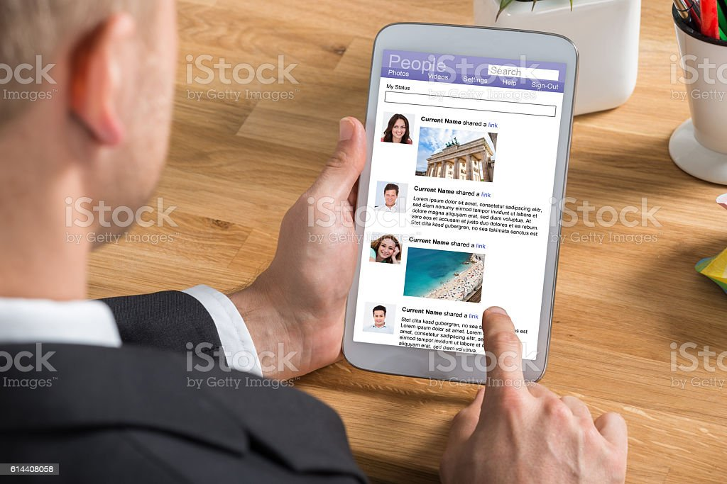 Businessman Using Social Networking Site On Digital Tablet stock photo
