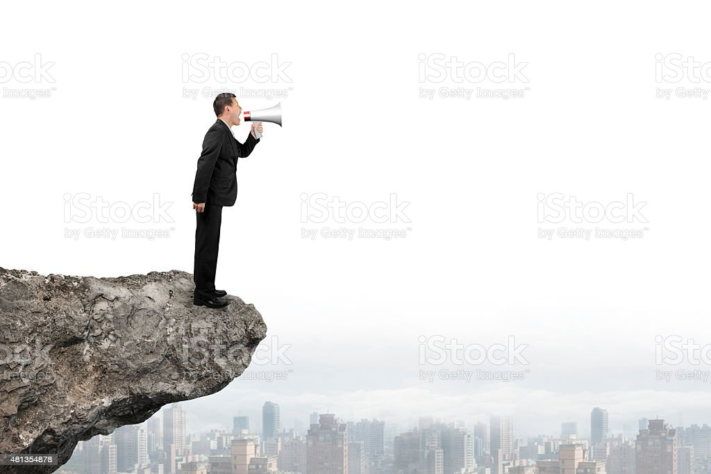 Businessman using speaker yelling on cliff with city skyline stock photo