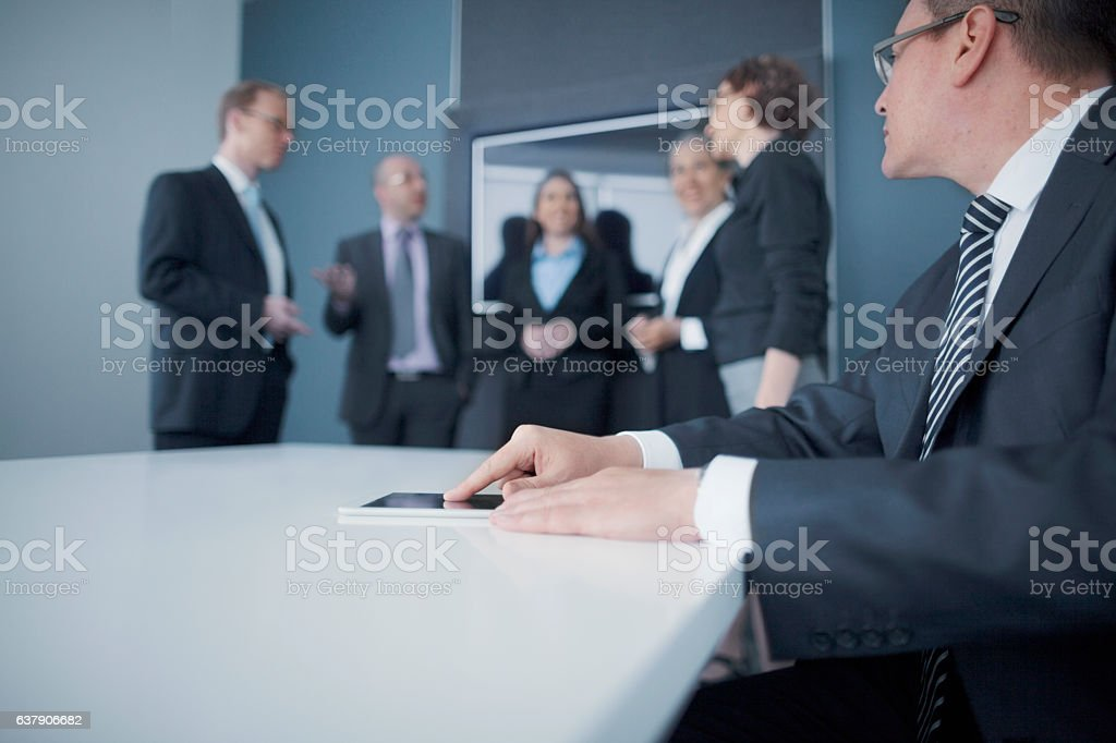 Businessman using tablet computer in office meeting stock photo