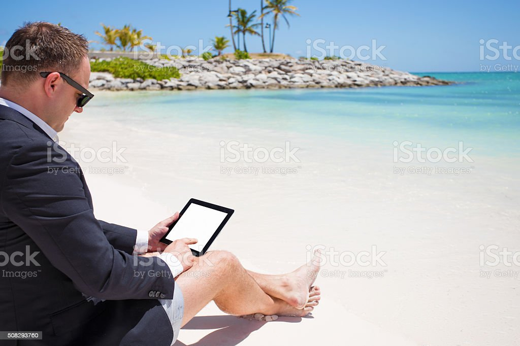 Businessman using tablet computer on the beach stock photo
