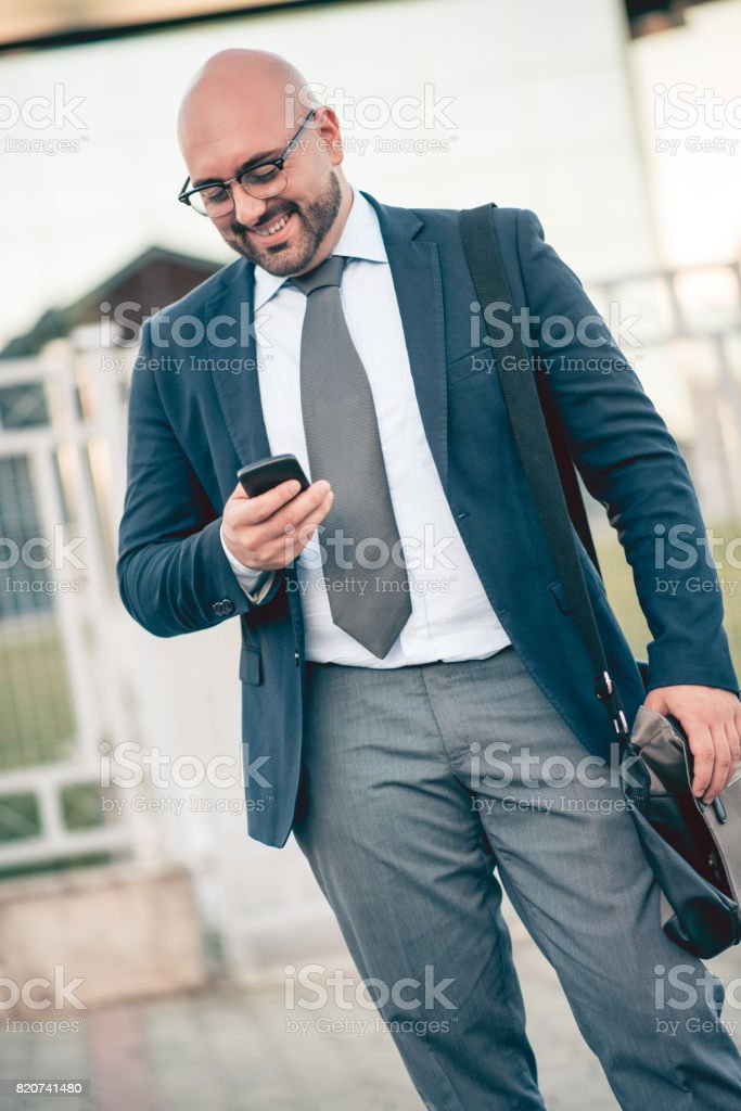 Businessman using Tablet Computer Standing outside of Office Building stock photo
