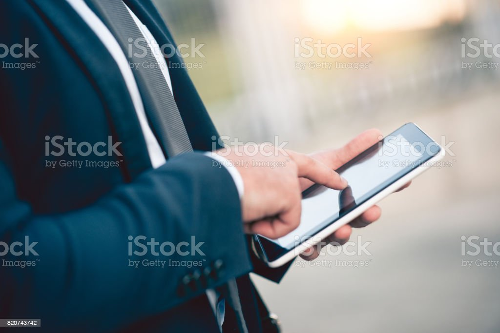 Businessman Using Tablet Outdoors, Doing Business the Modern Way stock photo