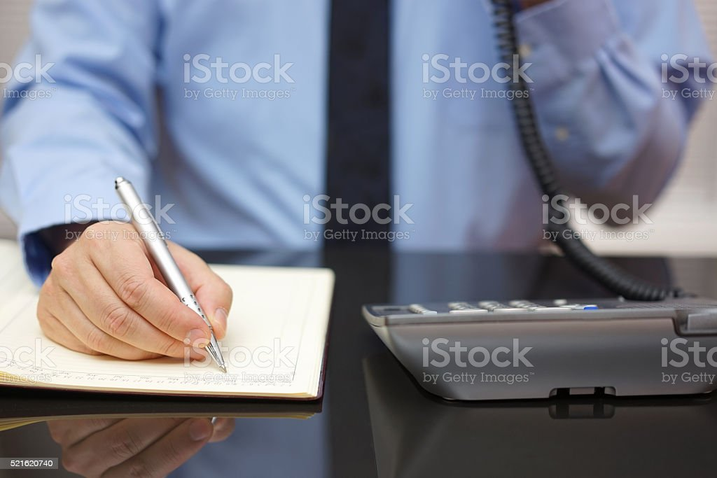 Businessman using telephone while writing in notebook  at desk stock photo