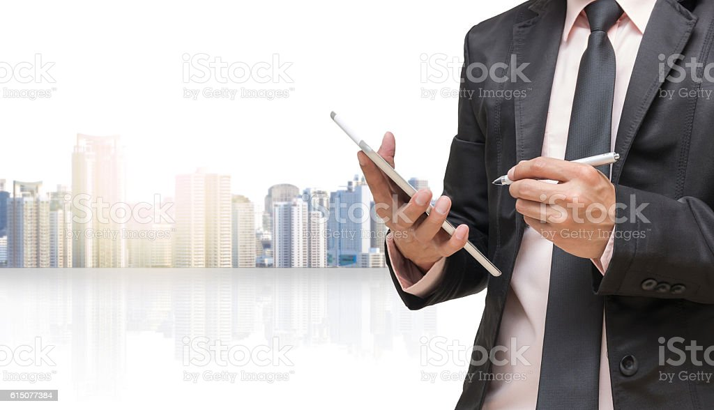 Businessman using the tablet on cityscape blurred background stock photo