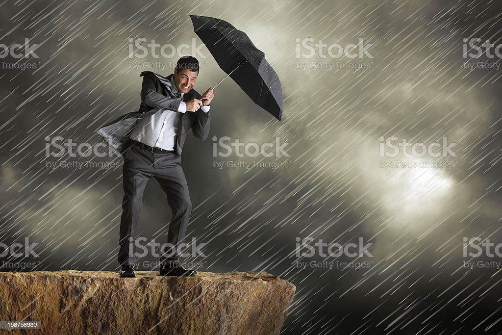 Businessman using umbrella for protection against driving rain royalty-free stock photo