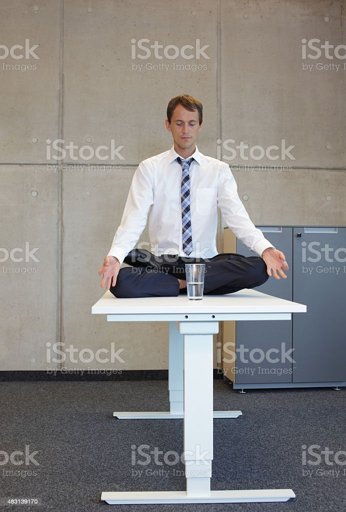 businessman v3.0 - meditating in lotus pose in office stock photo