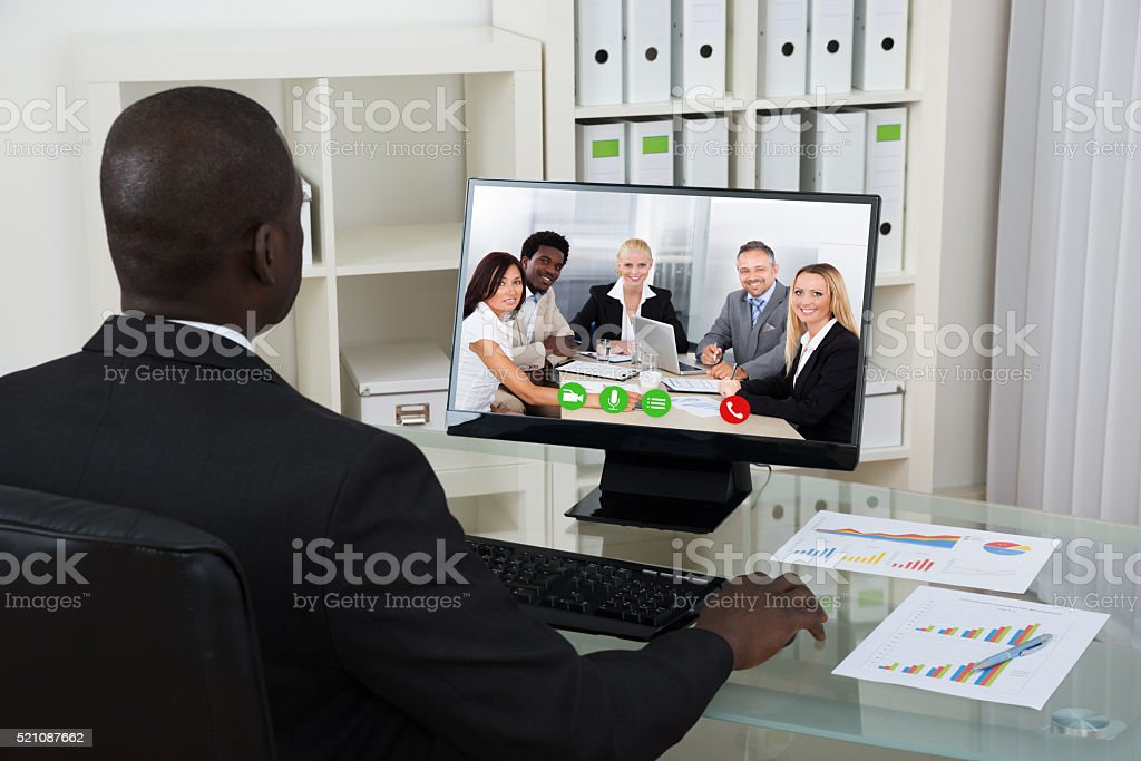 Businessman Video Chatting With Colleagues On Computer stock photo