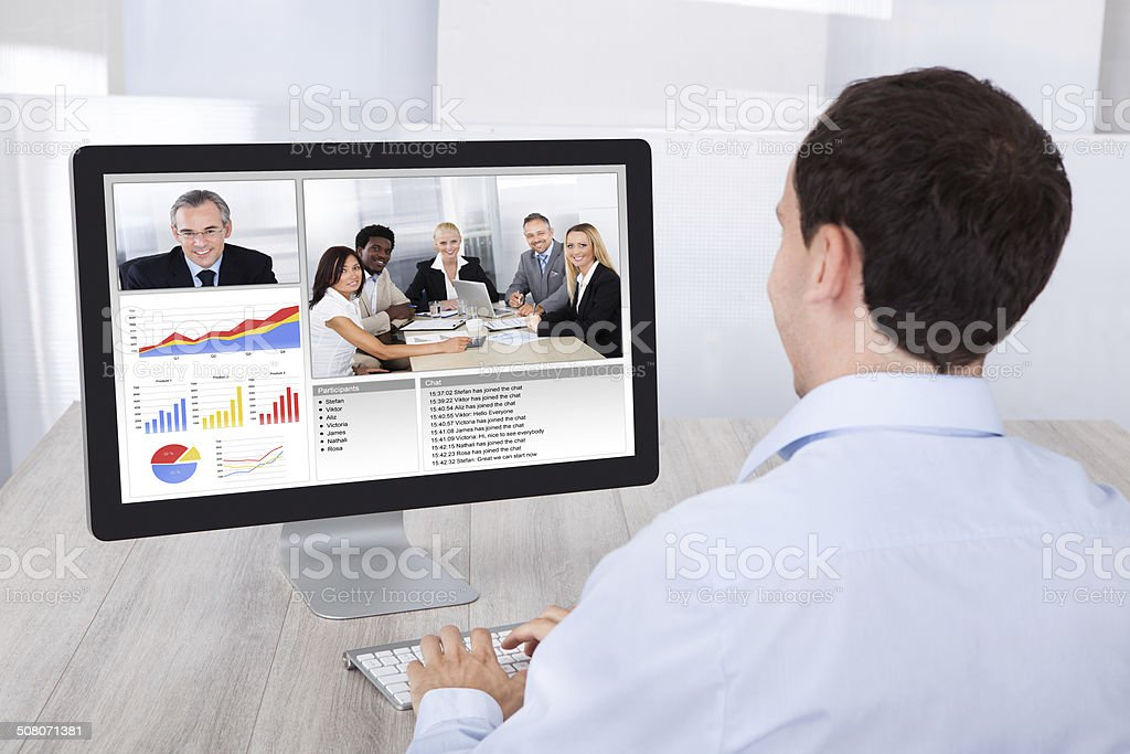Businessman Video Conferencing With Colleagues On Pc At Desk stock photo