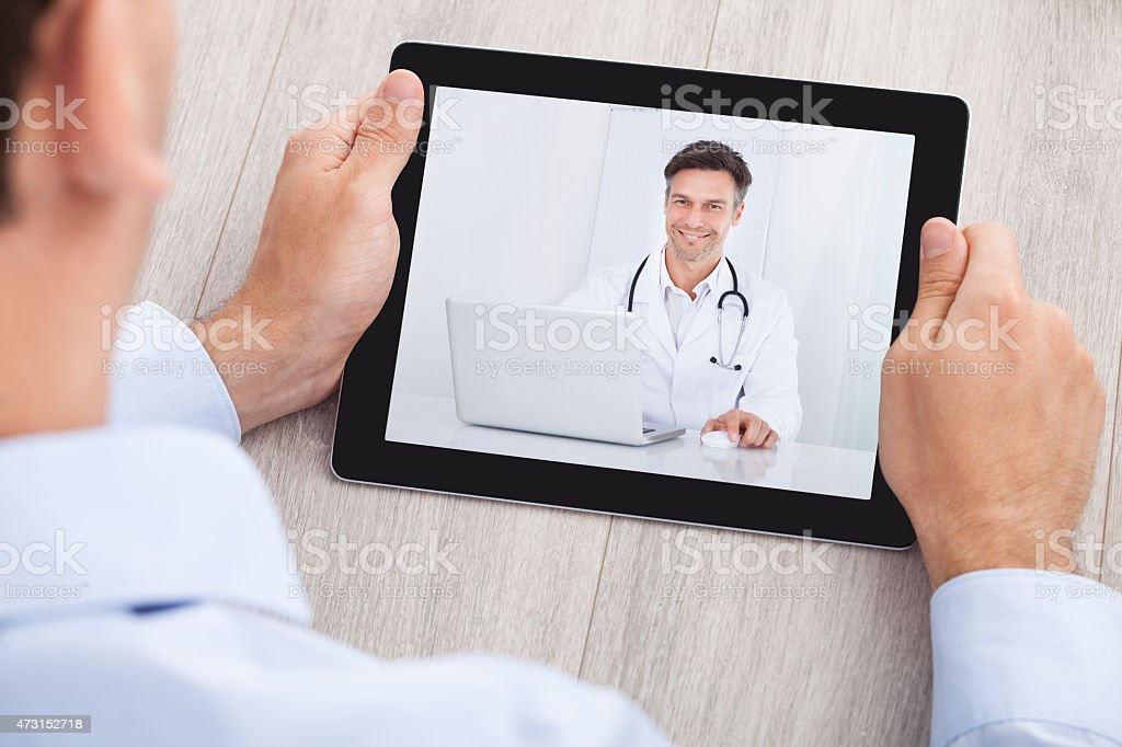 Businessman Video Conferencing With Doctor On Digital Tablet stock photo