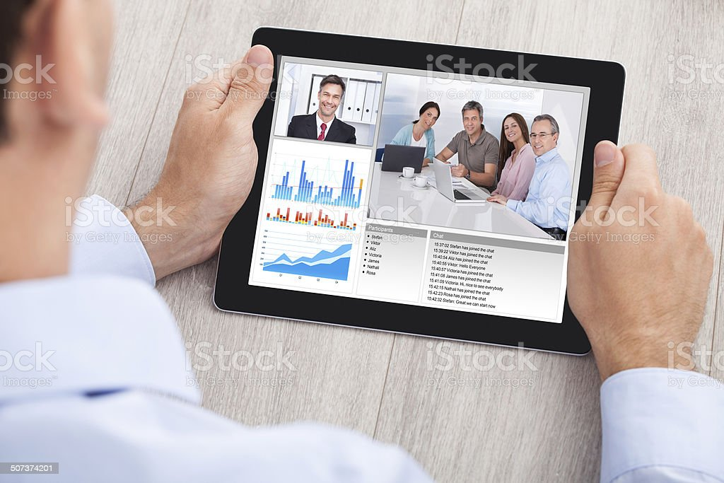 Businessman Video Conferencing With Team On Digital Tablet stock photo