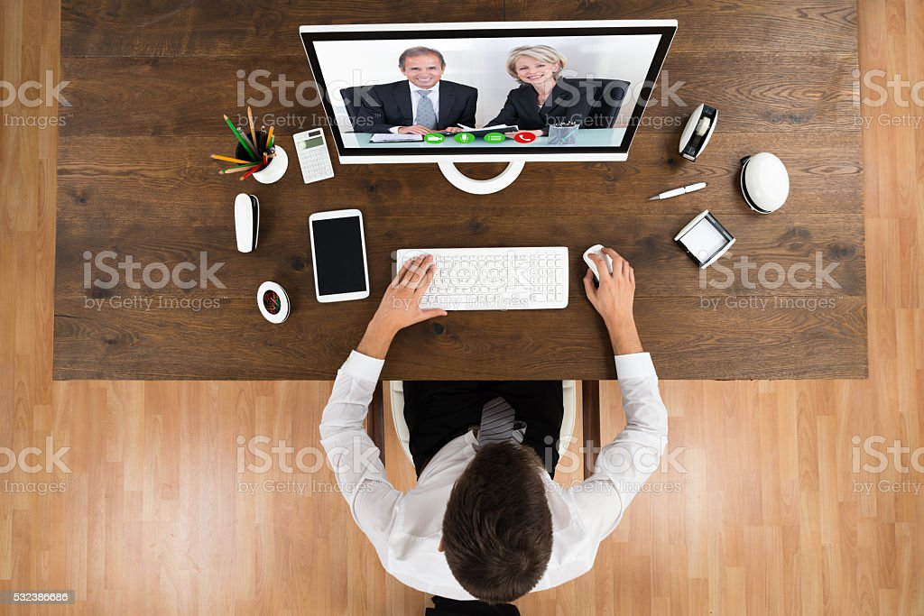 Businessman Videochatting With Senior Colleagues On Computer stock photo