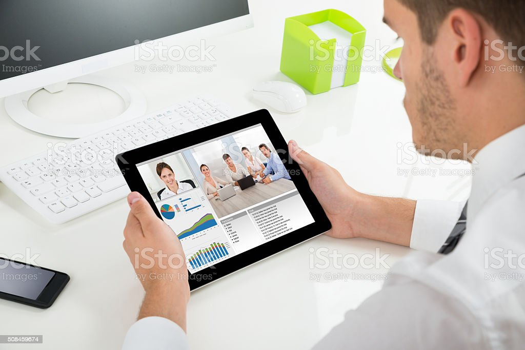 Businessman Videoconferencing With Colleagues On Digital Tablet stock photo