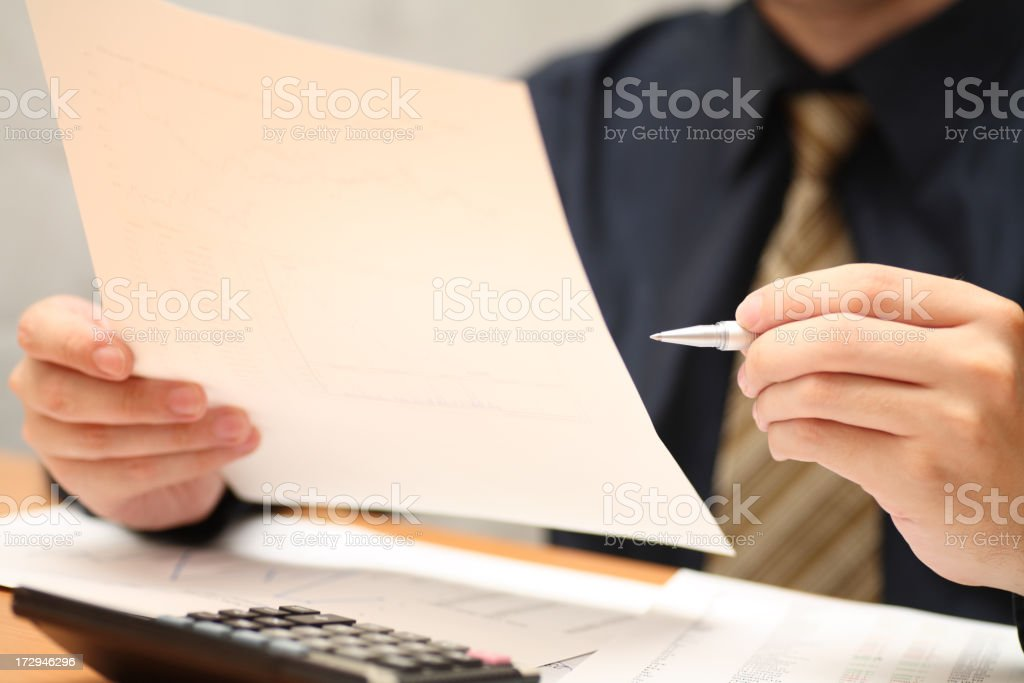Businessman viewing financial statements stock photo