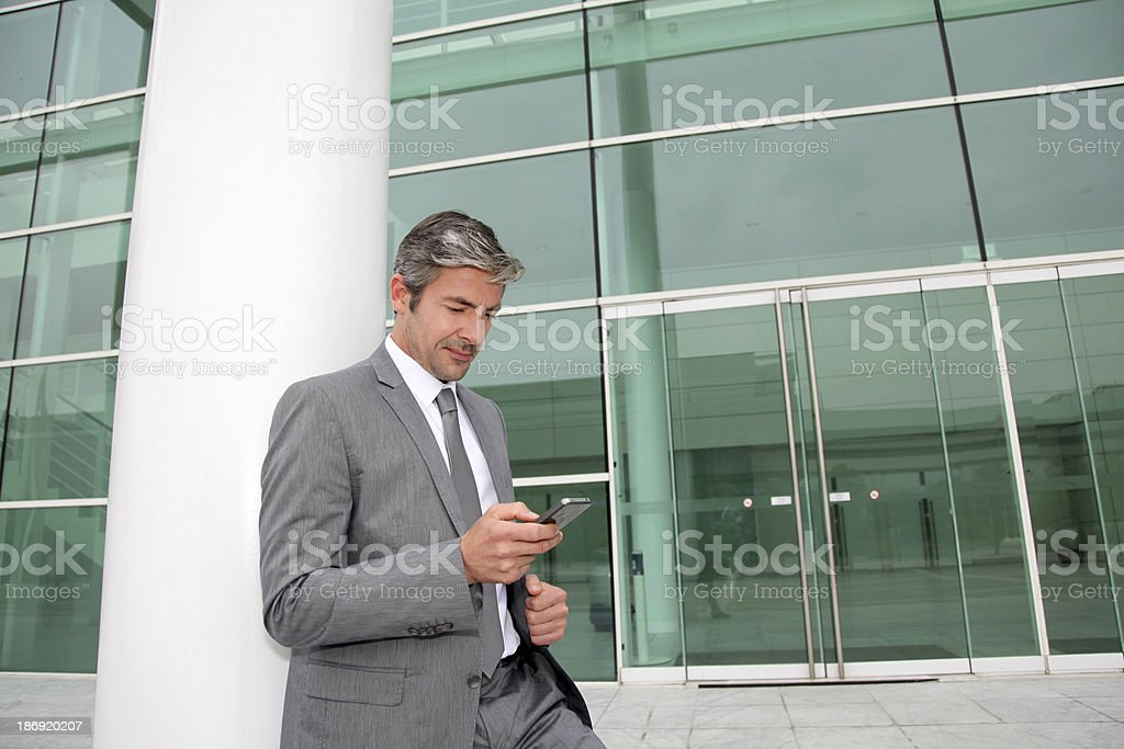 Businessman waiting client in front of buiding royalty-free stock photo