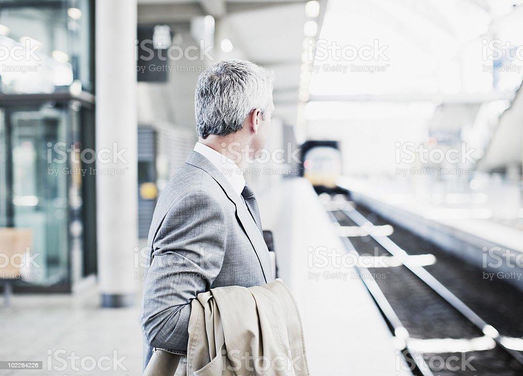 Businessman waiting for train on platform royalty-free stock photo