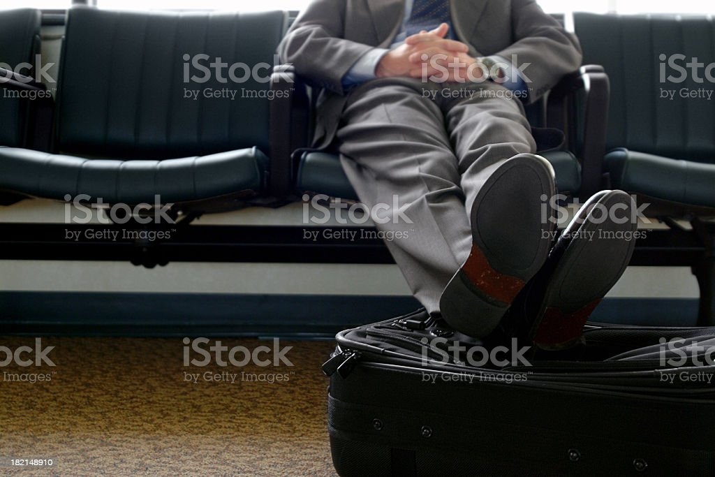 Businessman Waiting in Airport with His Feet Resting on Luggage royalty-free stock photo