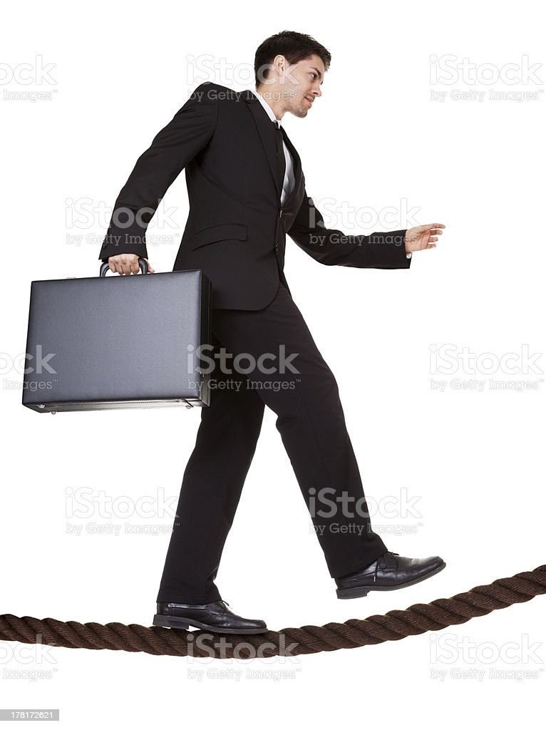 Businessman walking a tightrope royalty-free stock photo