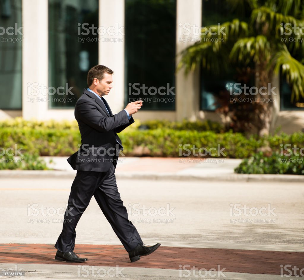 Businessman Walking and Texting on Street royalty-free stock photo