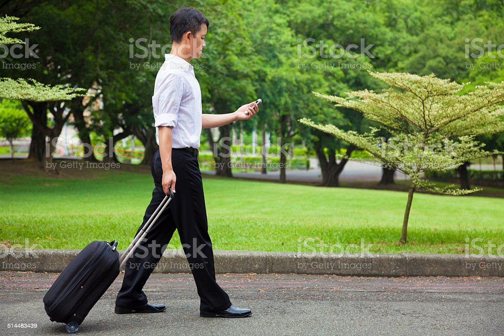 businessman walking and using a phone on the road stock photo
