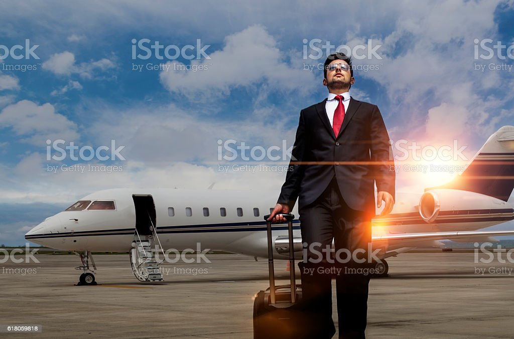 Businessman walking away from private jet after flight stock photo