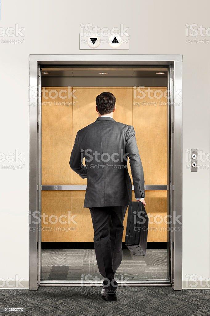 Businessman Walking Confidently Into Elevator stock photo