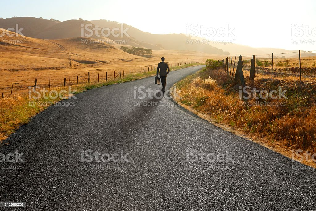 Businessman walking down curving rural road stock photo