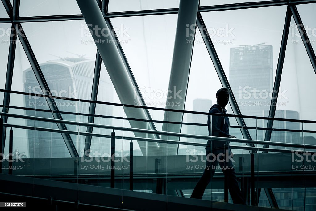 Businessman walking down stairs with London skyline in background stock photo