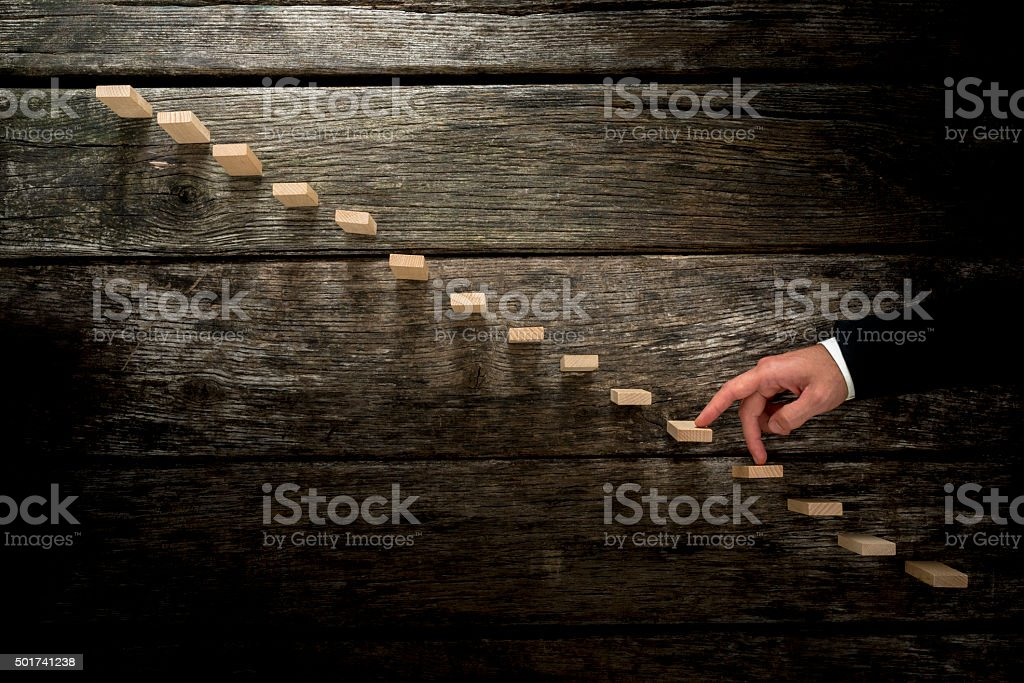 Businessman walking his fingers up wooden steps towards light stock photo