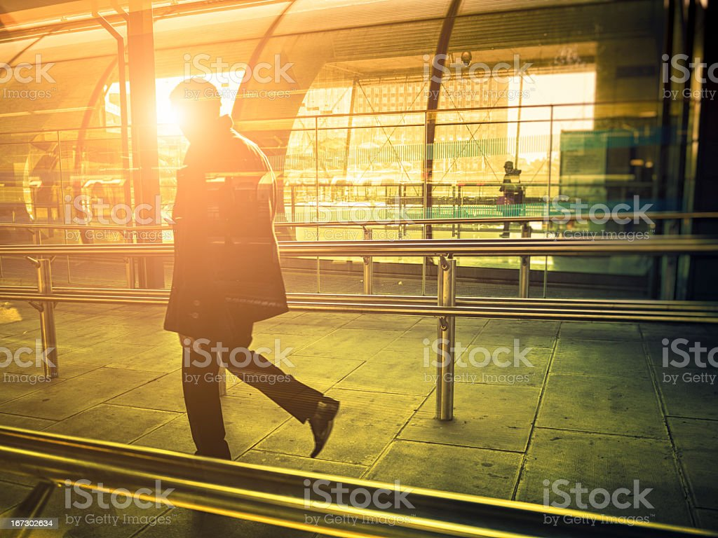Businessman walking in a contemporary station against sunlight, London stock photo