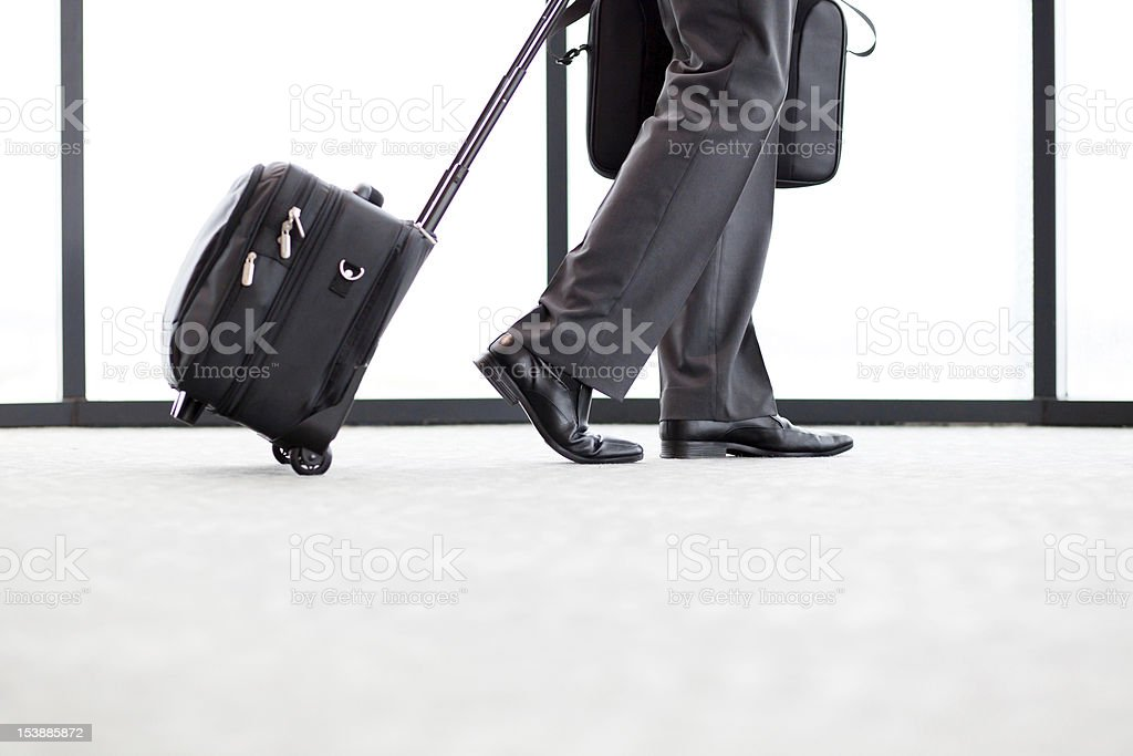 businessman walking in airport with luggage royalty-free stock photo