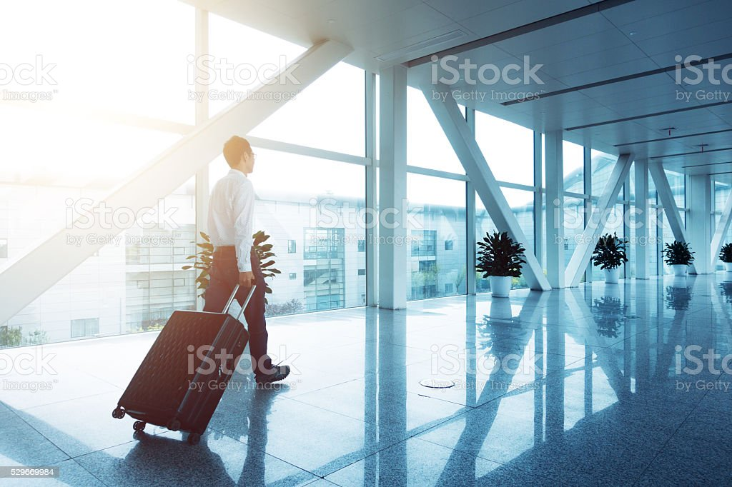 Businessman walking in airport with luggage stock photo