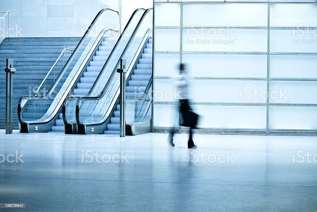 Businessman Walking in Blue Corridor With Escalator royalty-free stock photo