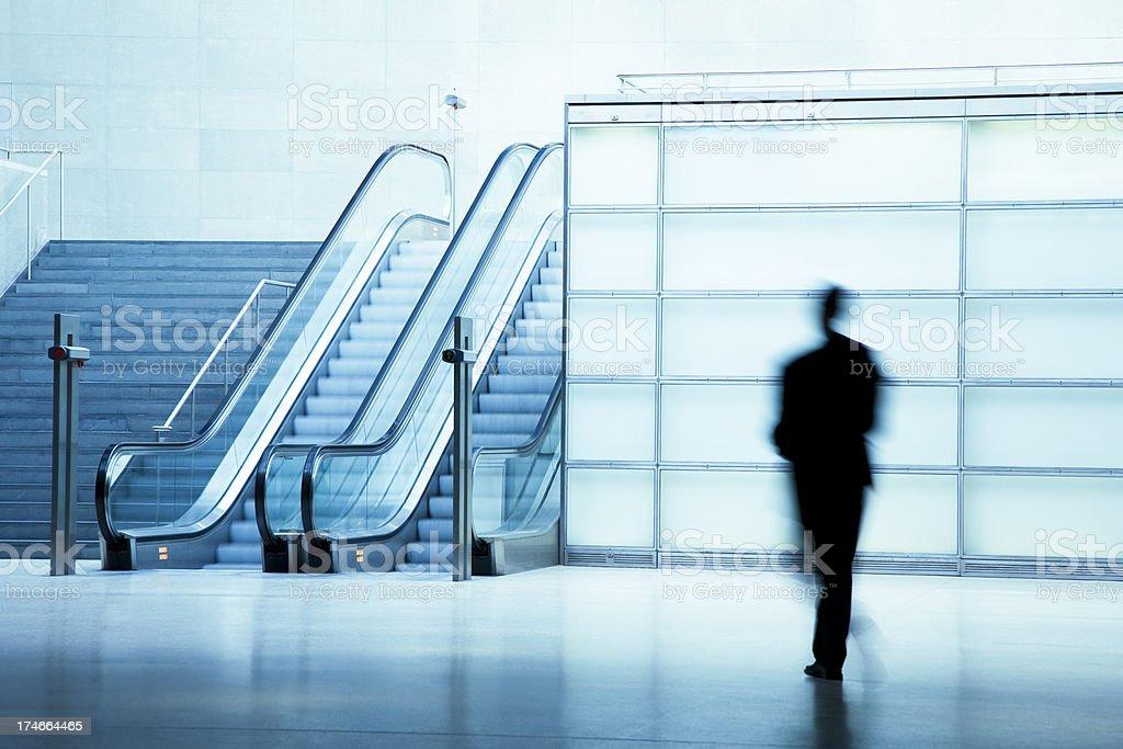 Businessman Walking in Blue Corridor With Escalator royalty-free stock photo