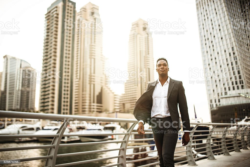 Businessman walking in dubai marina stock photo