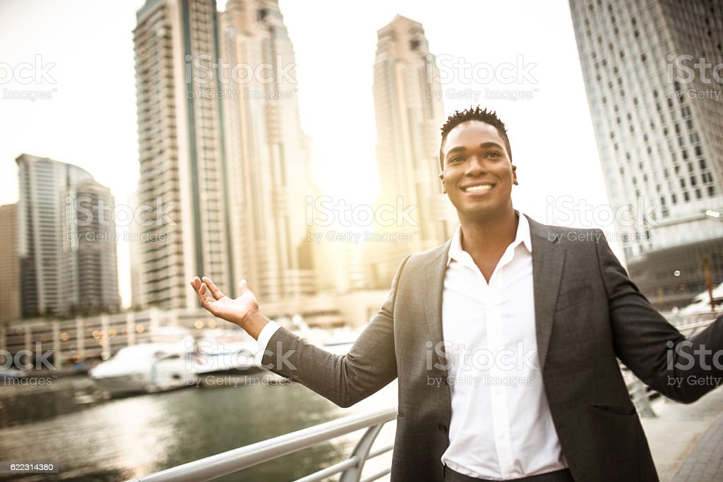 Businessman walking in dubai marina stock photo