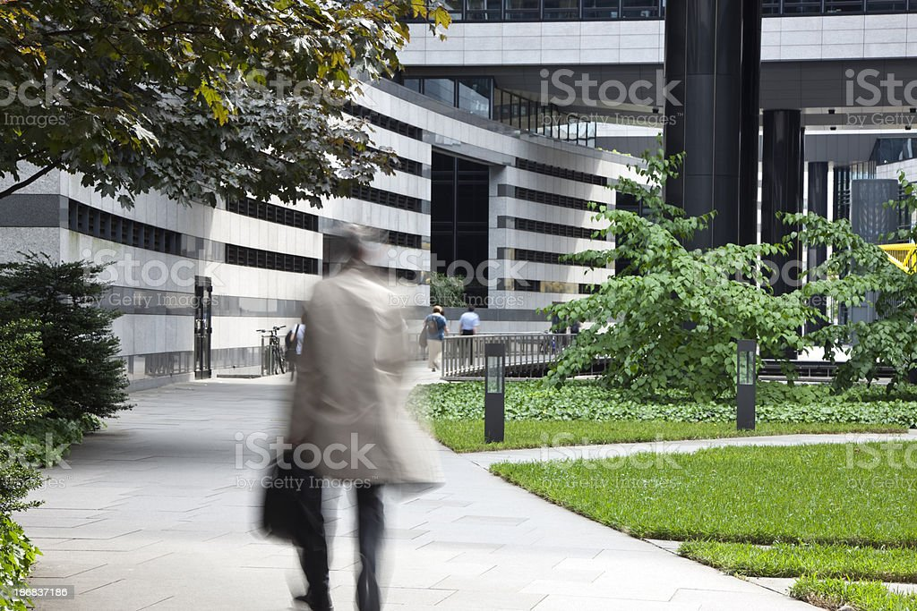 Businessman Walking in Financial District, Carrying Suitcase, Motion Blur royalty-free stock photo