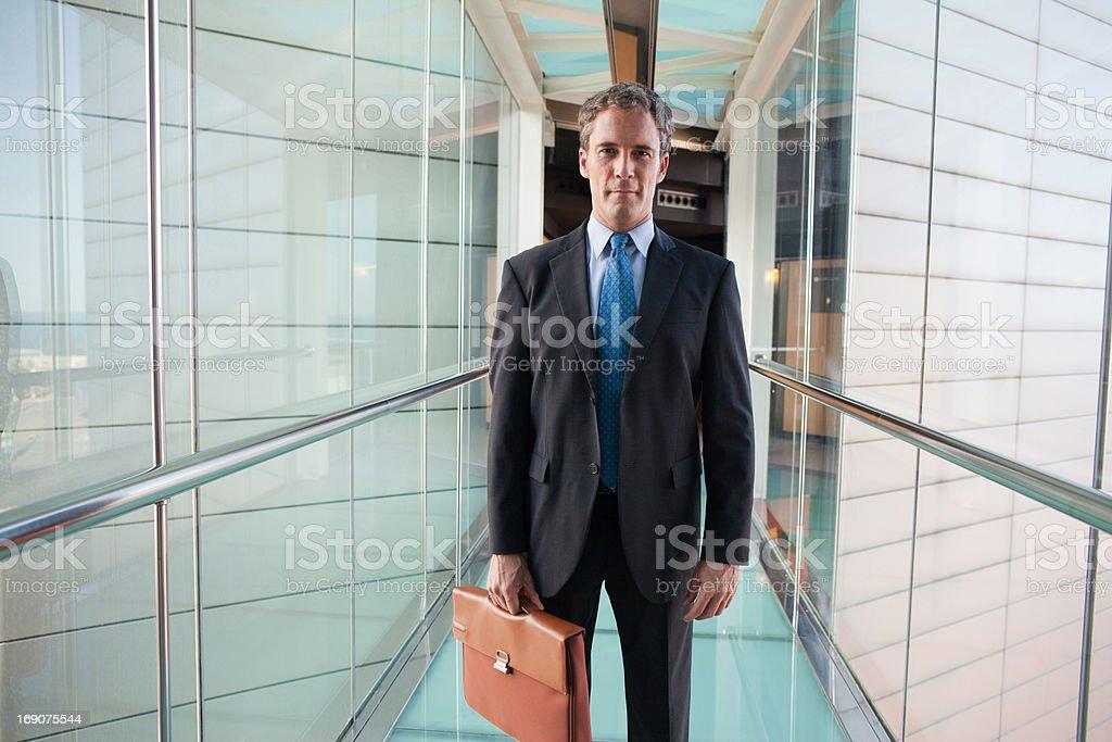 Businessman walking in glass skyway royalty-free stock photo
