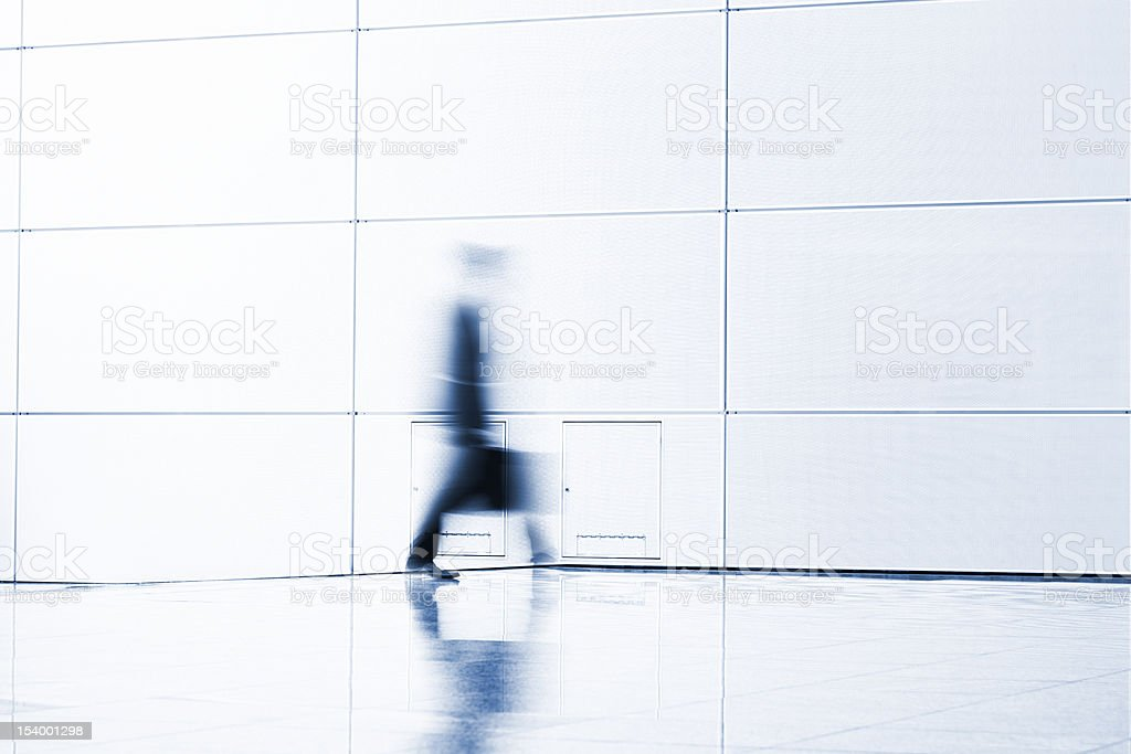 Businessman walking indoors, carrying suitcase, blurred motion, high key royalty-free stock photo