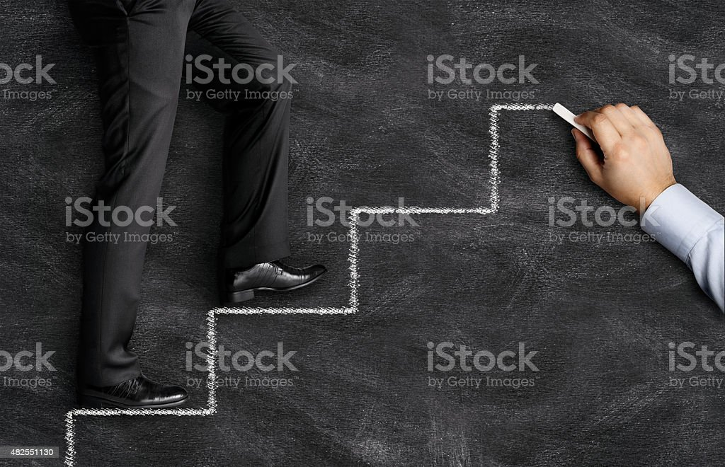 Businessman walking on drawing stairs stock photo