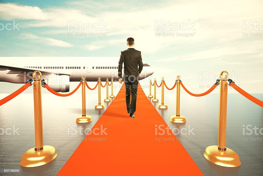 Businessman walking on red carpet stock photo