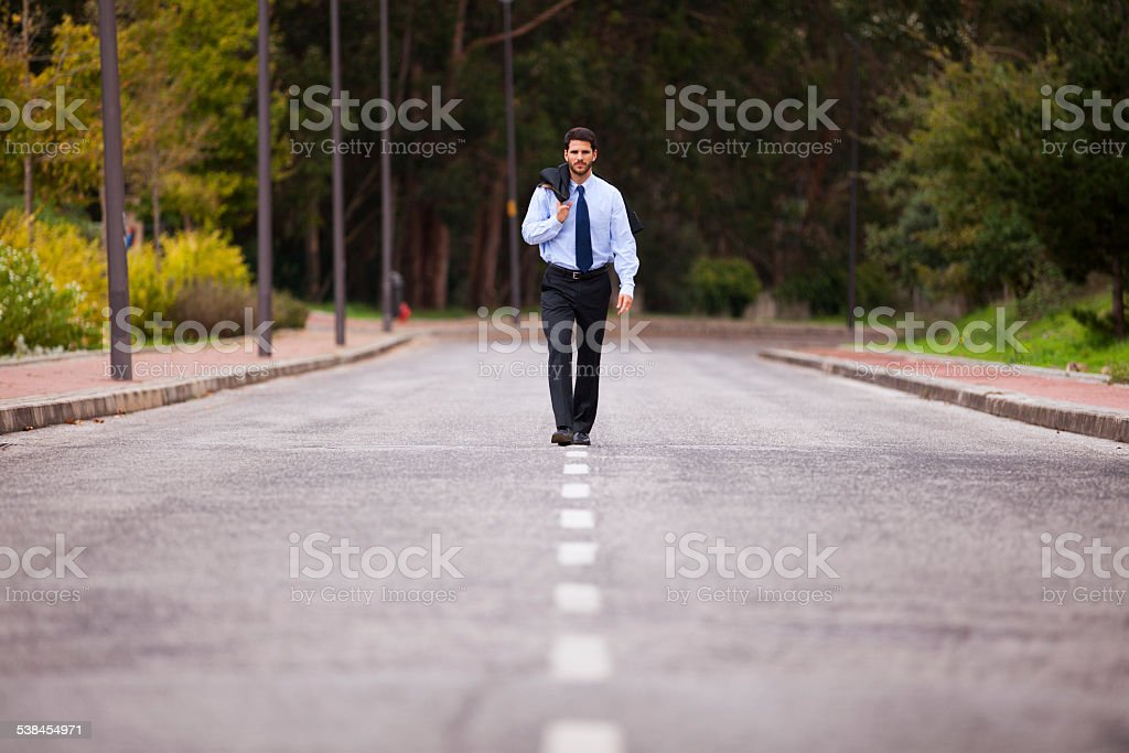 Businessman walking on the road line stock photo