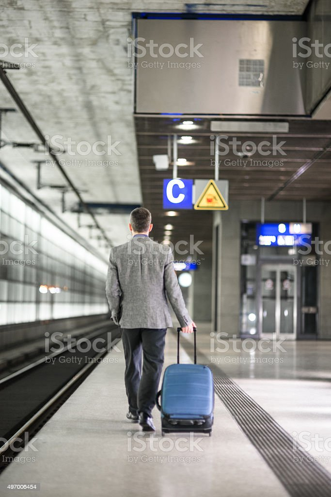 businessman walking on the train platform at the station stock photo