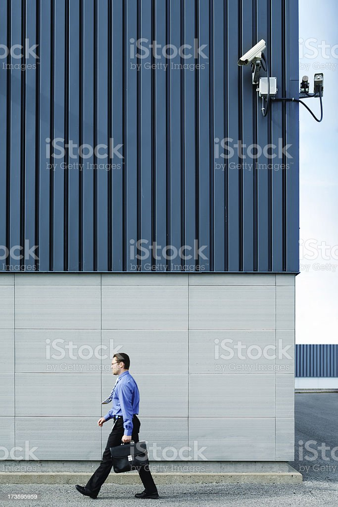 Businessman walking outside in front of security camera royalty-free stock photo