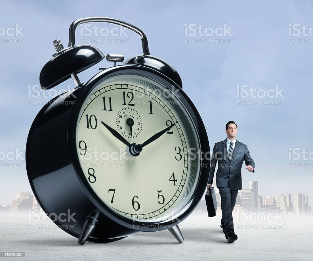 Businessman walking past a large alarm clock stock photo