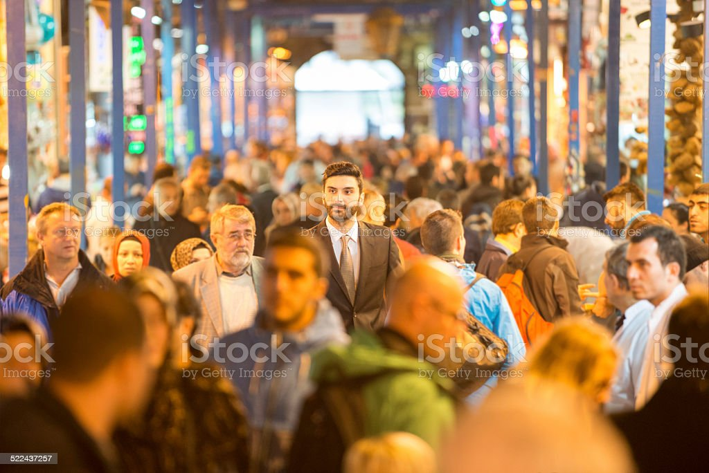 Businessman walking through bazaar stock photo