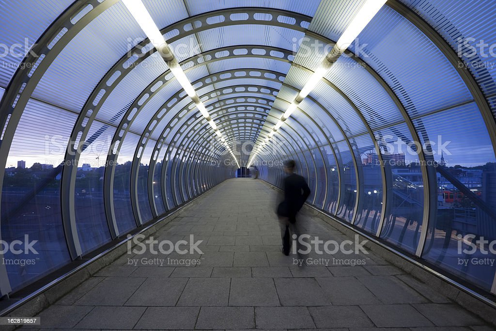 Businessman Walking Through Glass Skywalk at Twilight stock photo