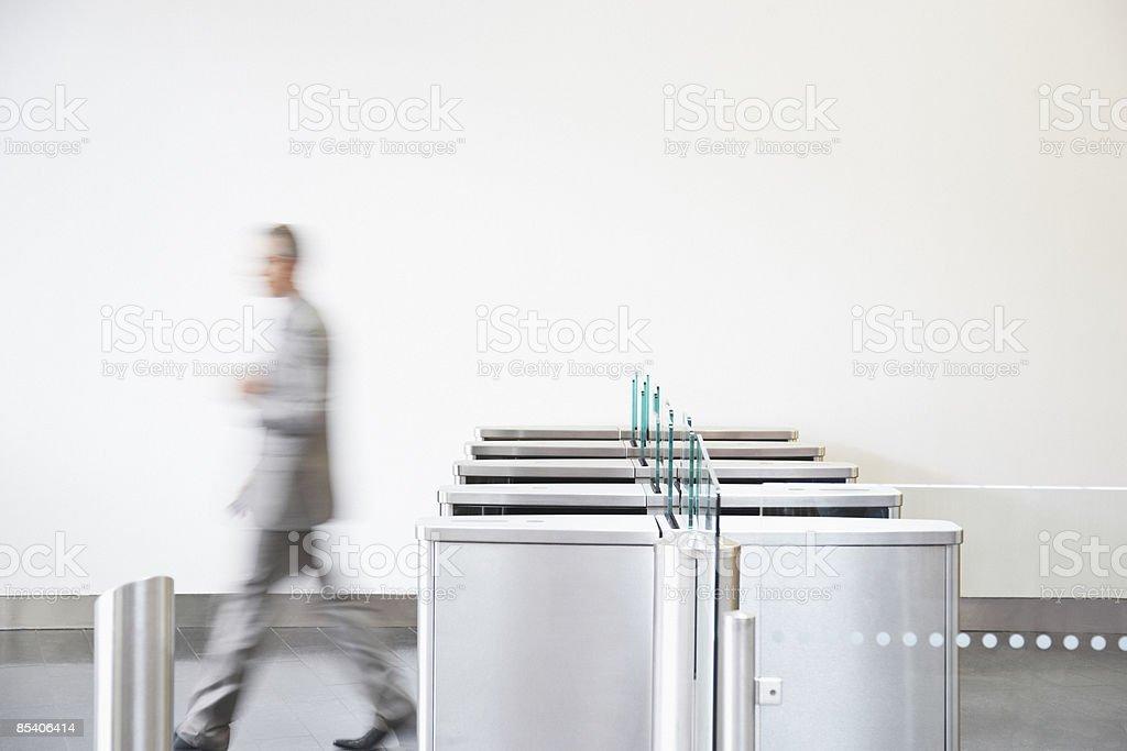 Businessman walking through turnstile stock photo