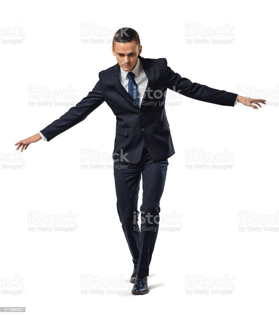 Businessman walking tightrope or border, isolated on white background. stock photo